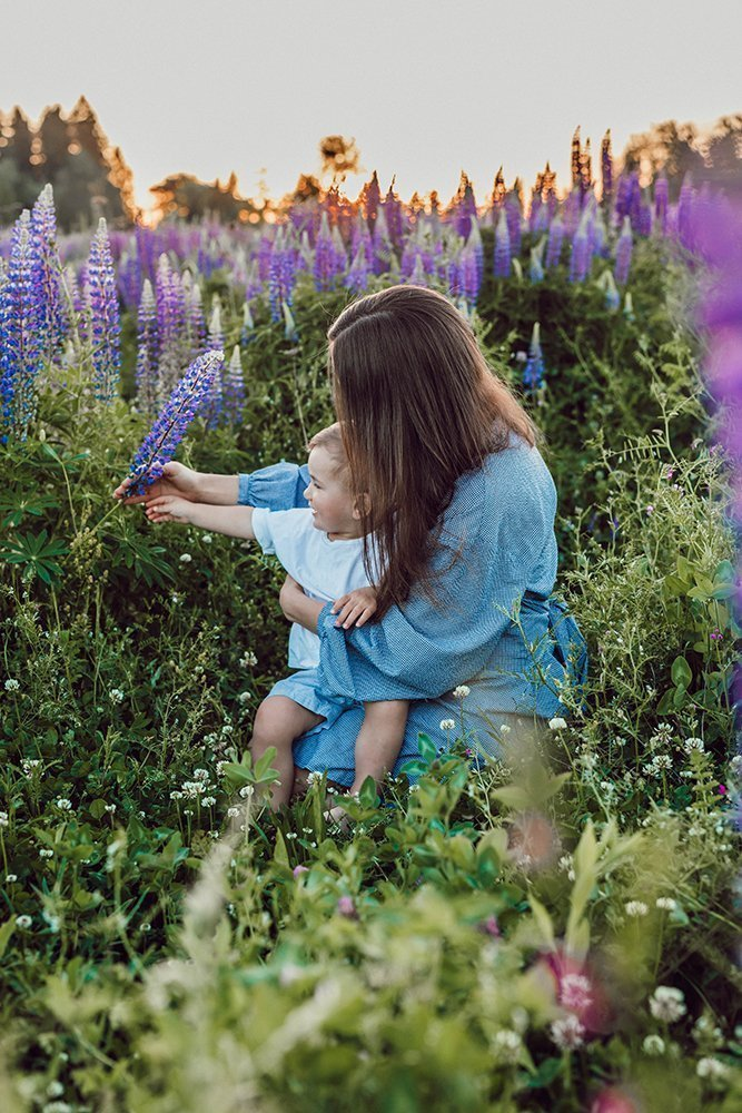 Mom holding toddler in field of flowers
