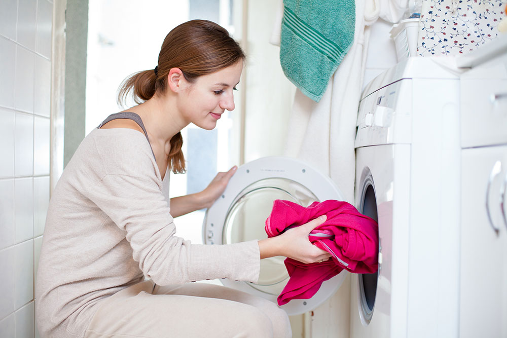 mom putting laundry in the washing machine